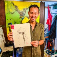Hoi An - Artist Ha Duong posing with one of his drawing (that we bought!)